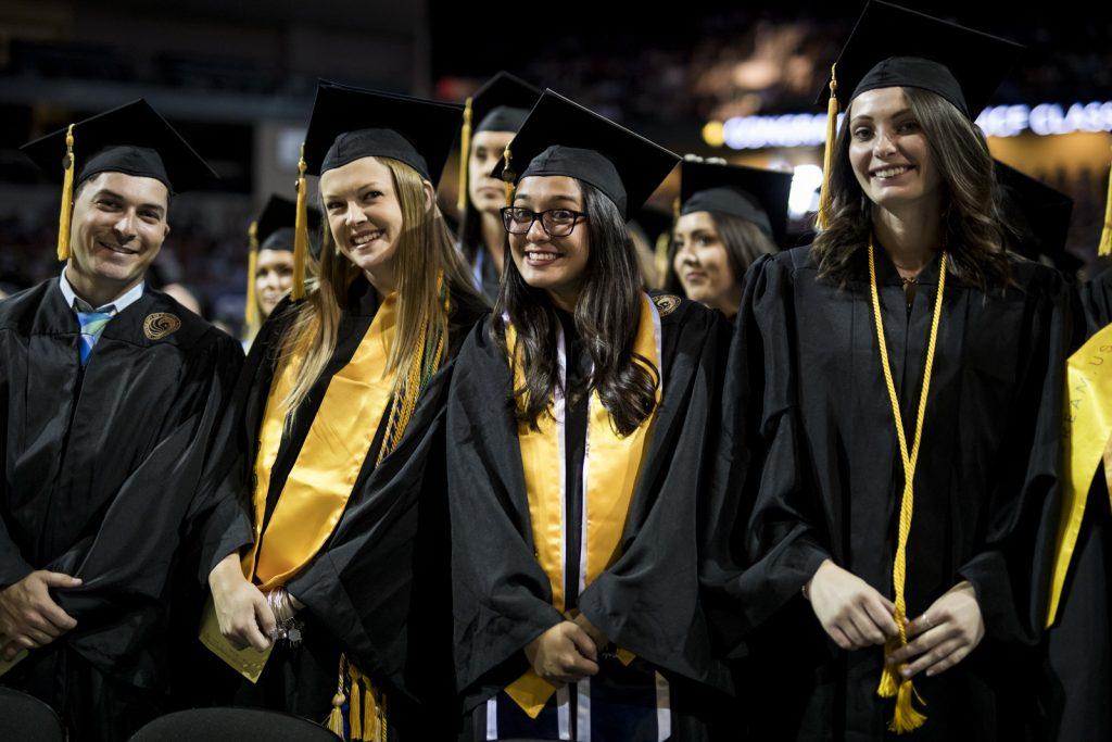 Group of 4 UCF graduates in academic regalia