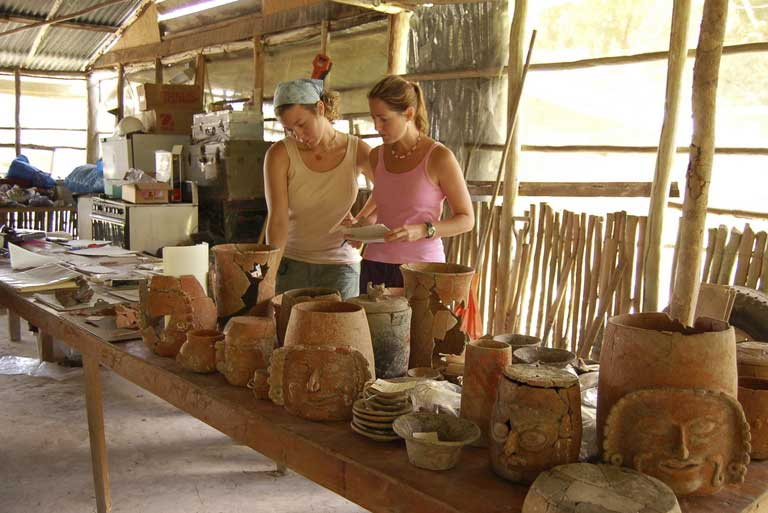 Students examining ancient Mayan pottery